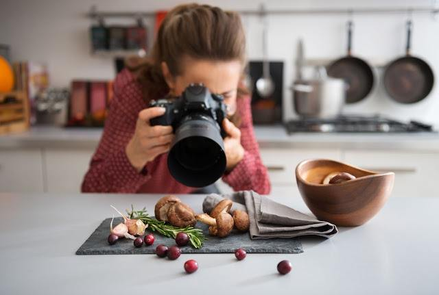 40568382 - a woman food photographer in the background leans down to take a close-up, in a modern kitchen, of autumn fruits and vegetables - mushrooms, garlic, rosemary, and cranberries.